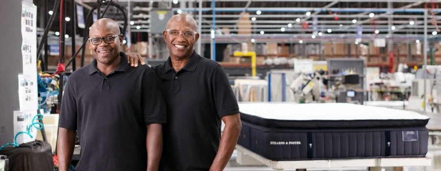 2 master craftsman smiling in front of a Stearns & Foster mattress