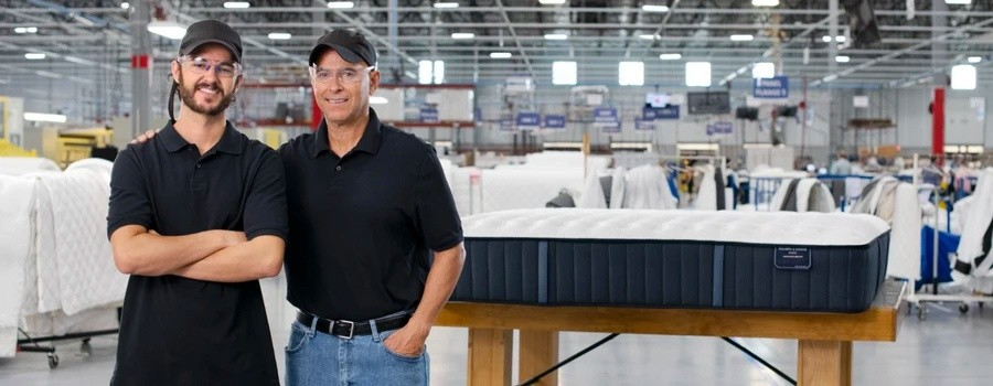 Father and son master craftsman standing in a Stearns & Foster factory in front of a newly completed mattress